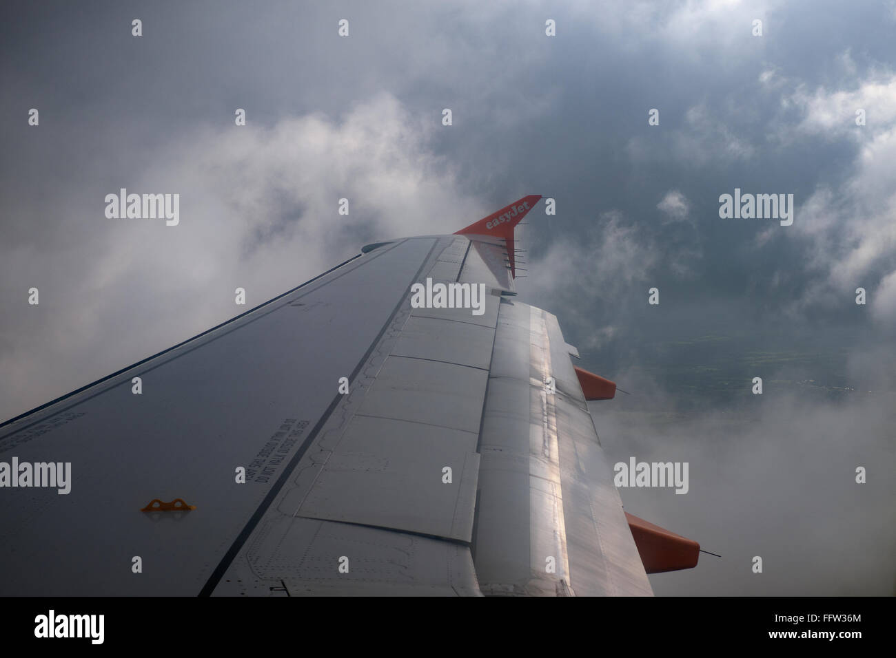 Easyjet wing tip in flight through clouds - Stock Image