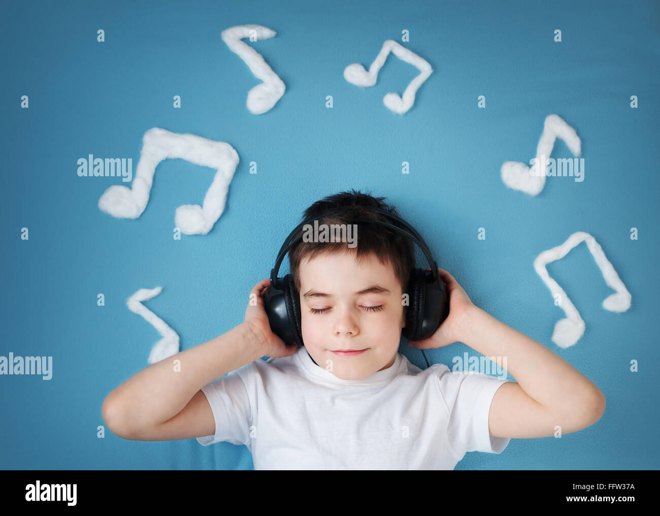 boy on blue blanket background with headphones - Stock Image