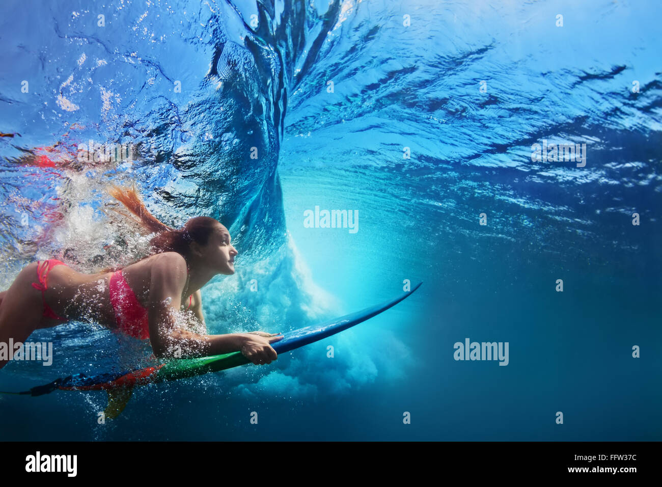Young girl in bikini - surfer with surf board dive underwater under big ocean wave. - Stock Image