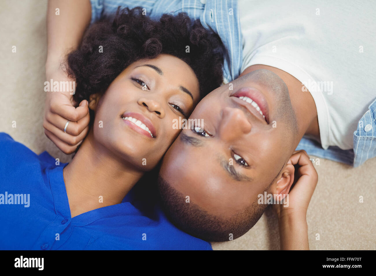Portrait of smiling couple lying on the floor - Stock Image