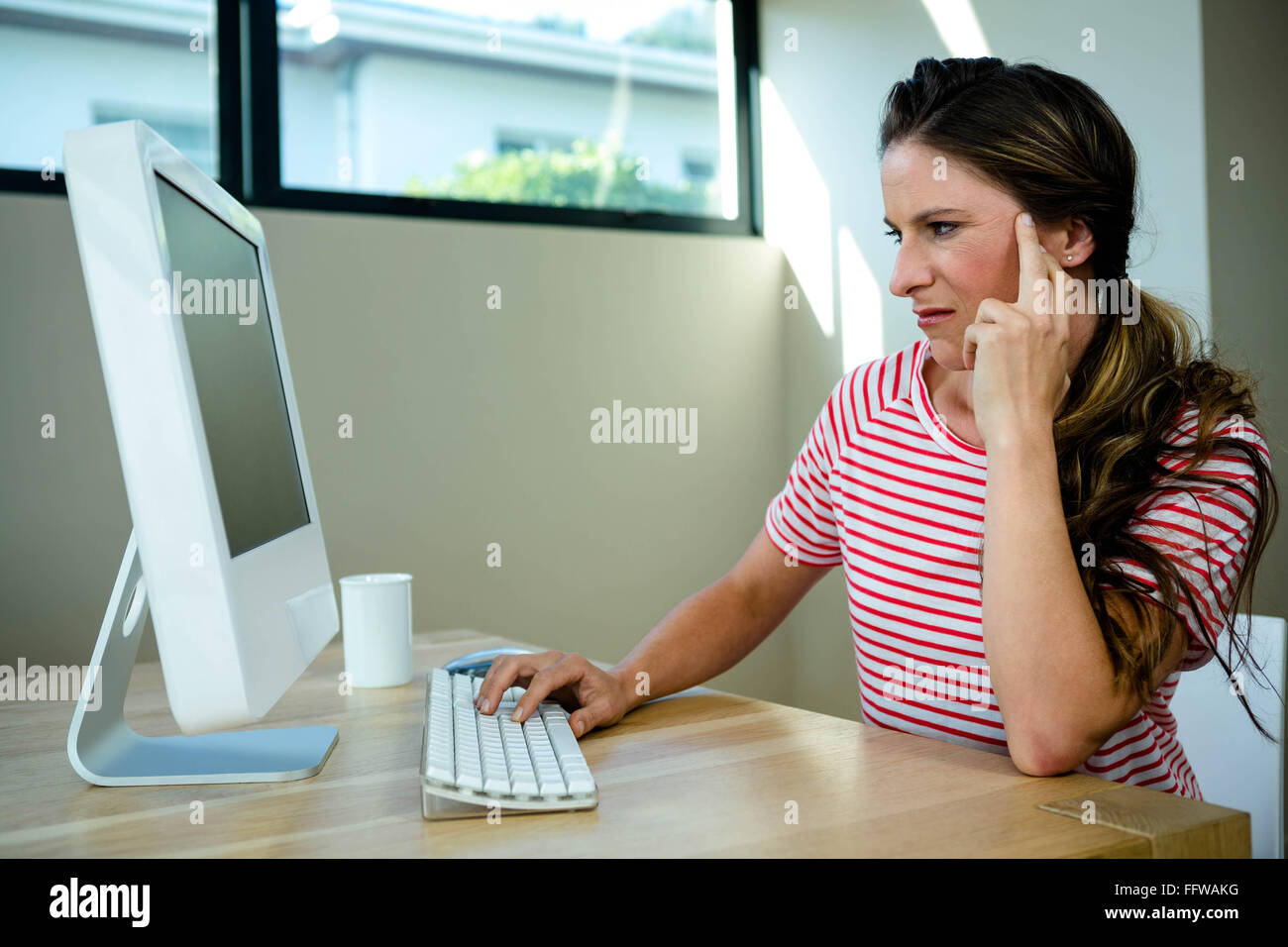 woman looking disgruntled sitting at her computer - Stock Image