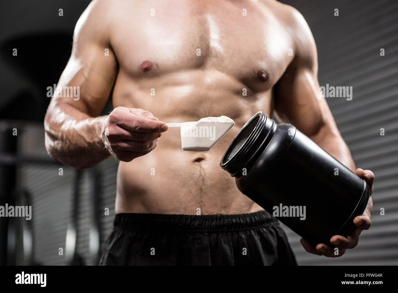Mid section of shirtless man taking proteins from can - Stock Image