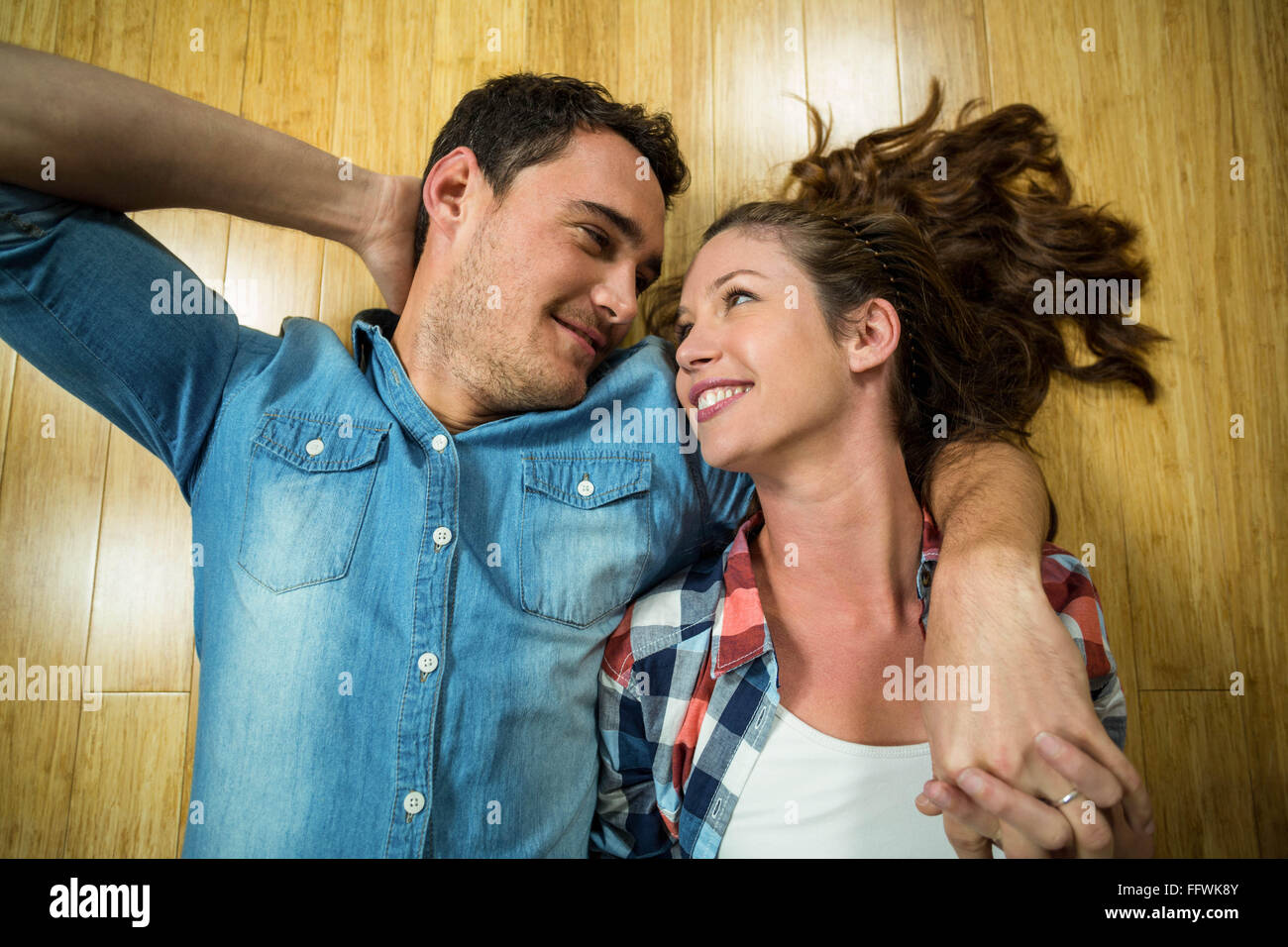 Young couple lying on floor in their house - Stock Image