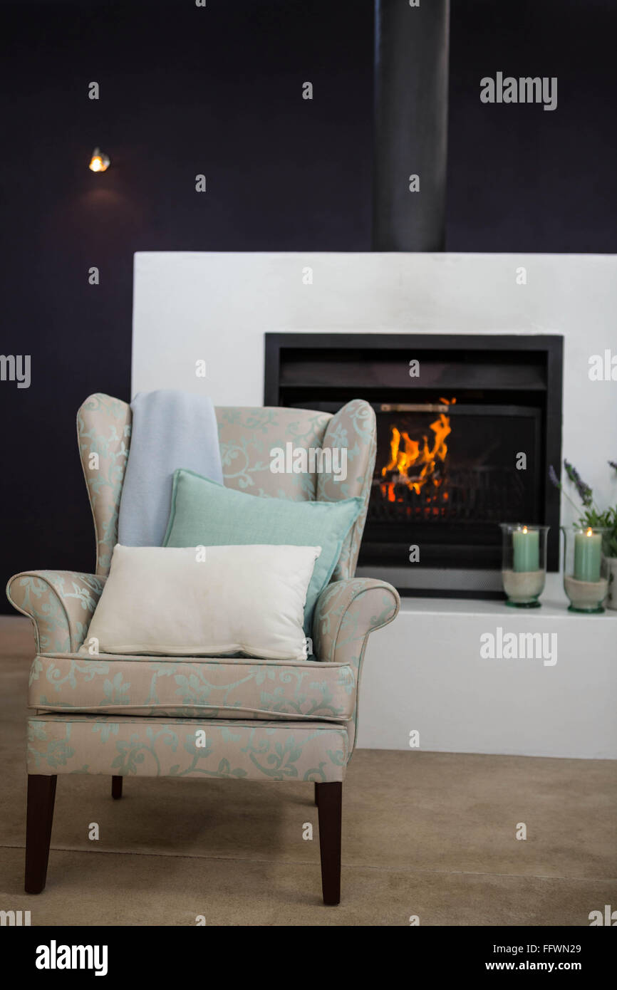 Armchair next to fireplace - Stock Image