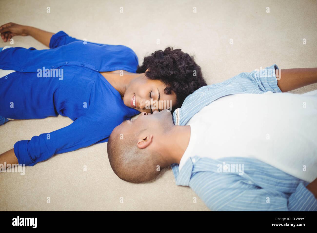 Peaceful couple lying on the floor - Stock Image