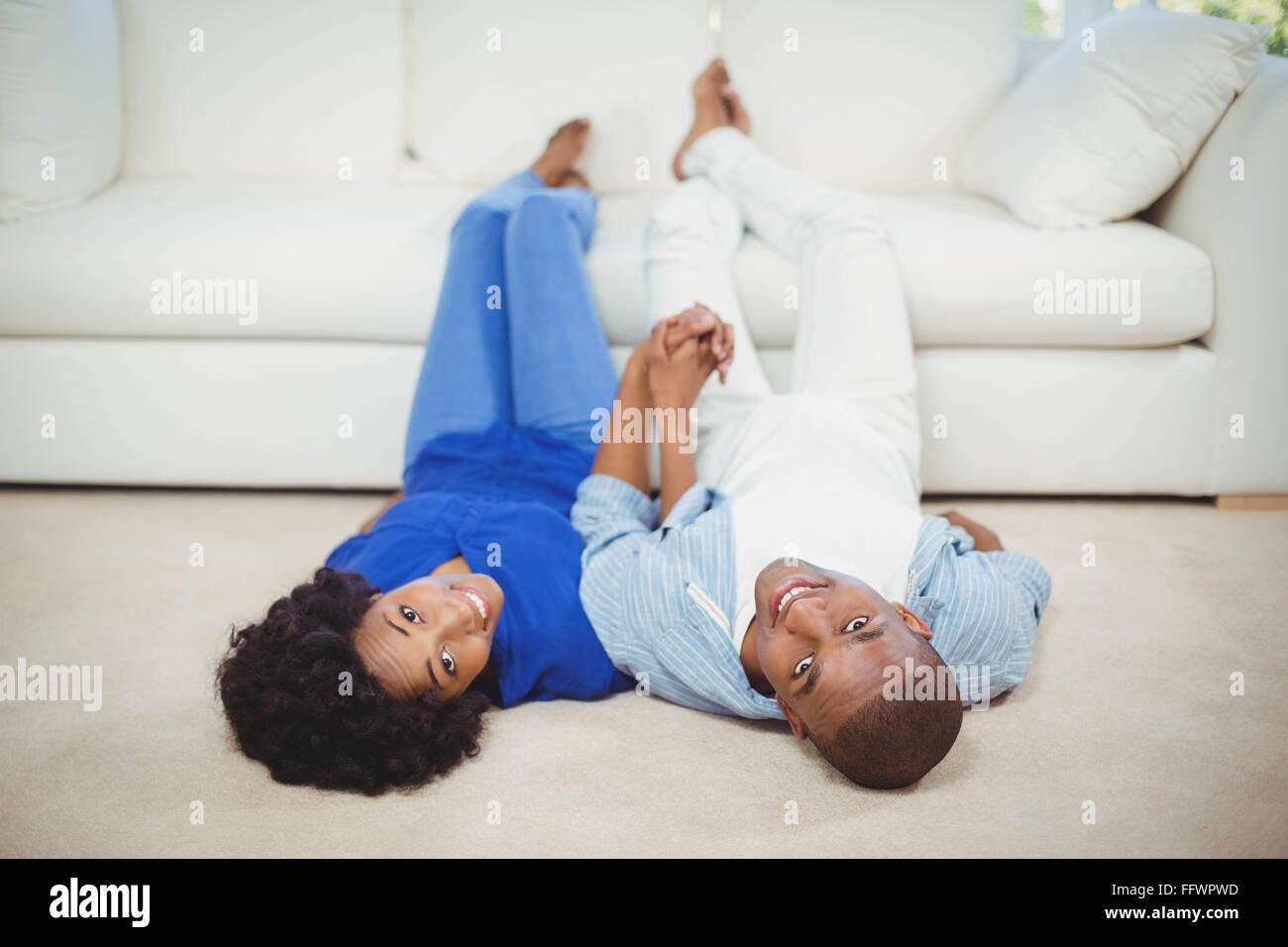 Happy couple lying on the floor - Stock Image