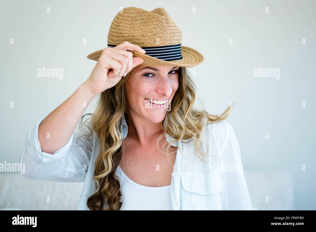 68a4cc3a8eb94 woman wearing a straw fedora smiling and looking away - Stock Image