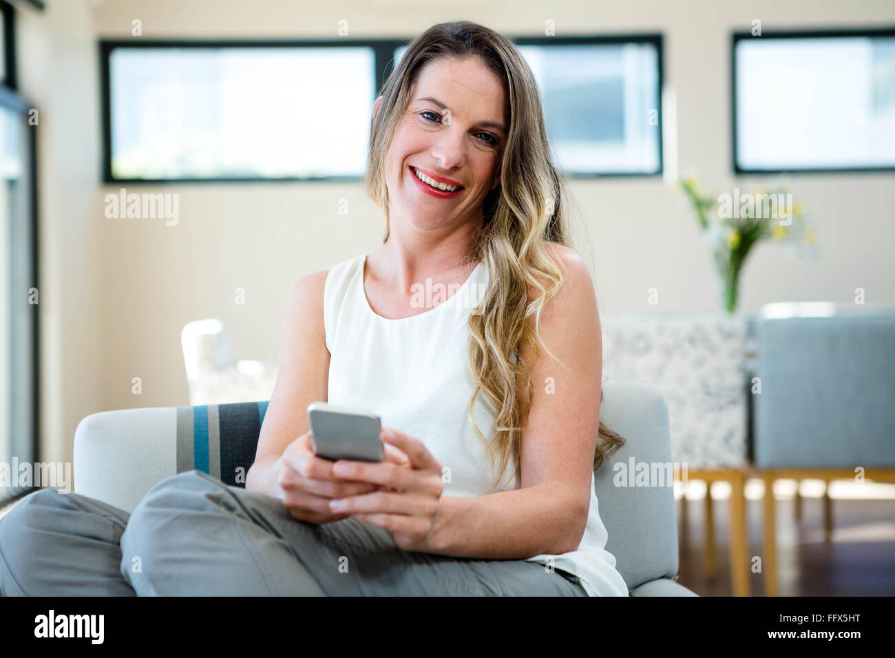 smiling woman on her mobile phone - Stock Image