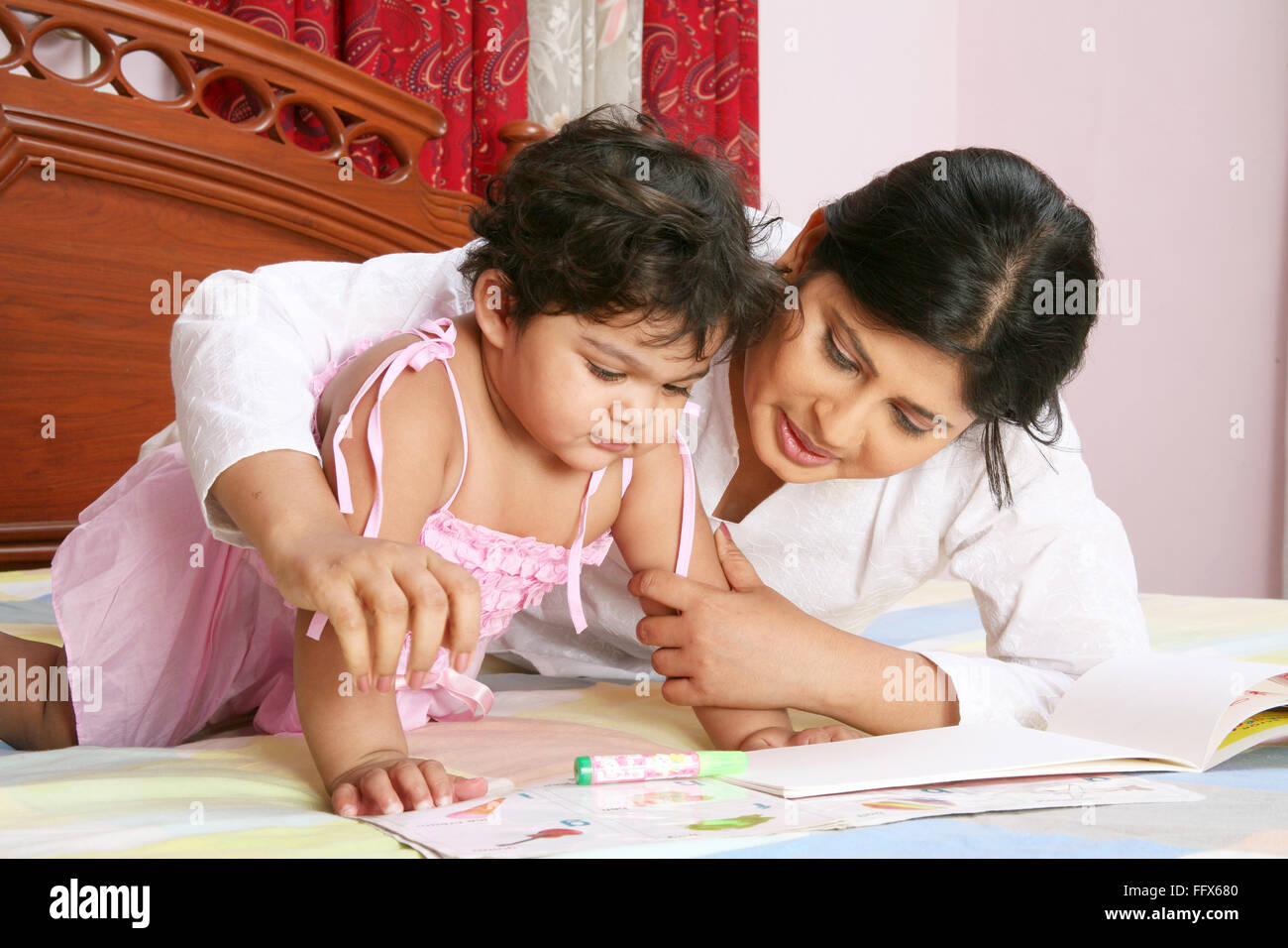 young mother telling story and teaching to baby girl of one and half year lying on bed with book - Stock Image