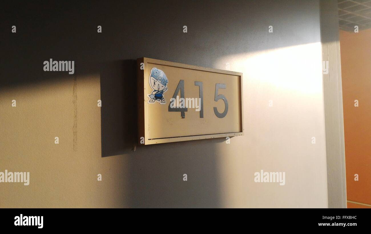 Close-Up Of Board On Wall With Number 415 And Cartoon - Stock Image