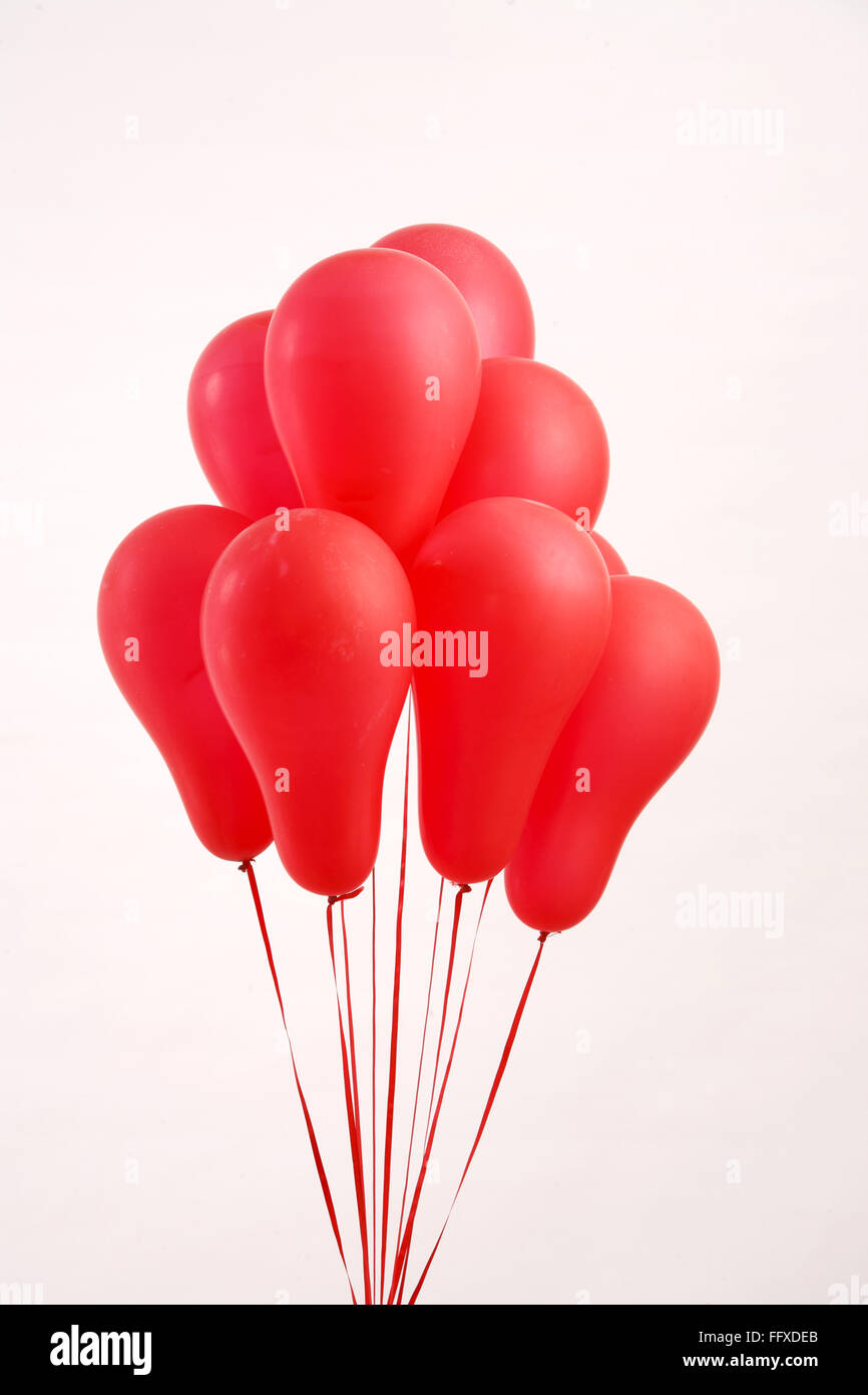 Bunch of red color gas balloons tied with red ribbons - Stock Image