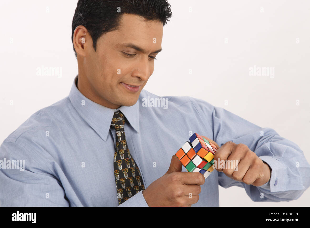 Businessman holding Rubik cube trying to solve puzzle MR#703T - Stock Image