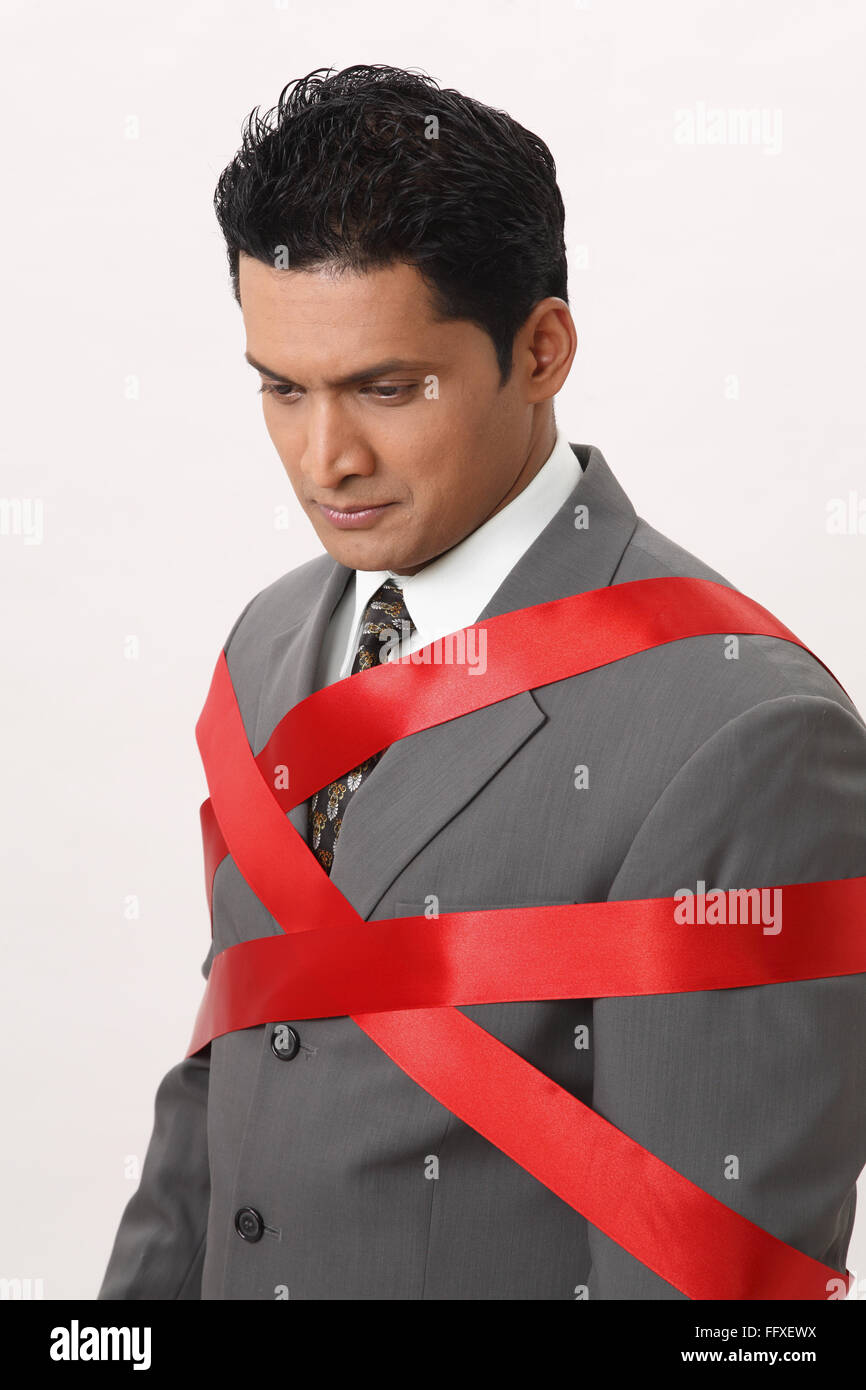 Businessman tied with red ribbon MR#703T - Stock Image