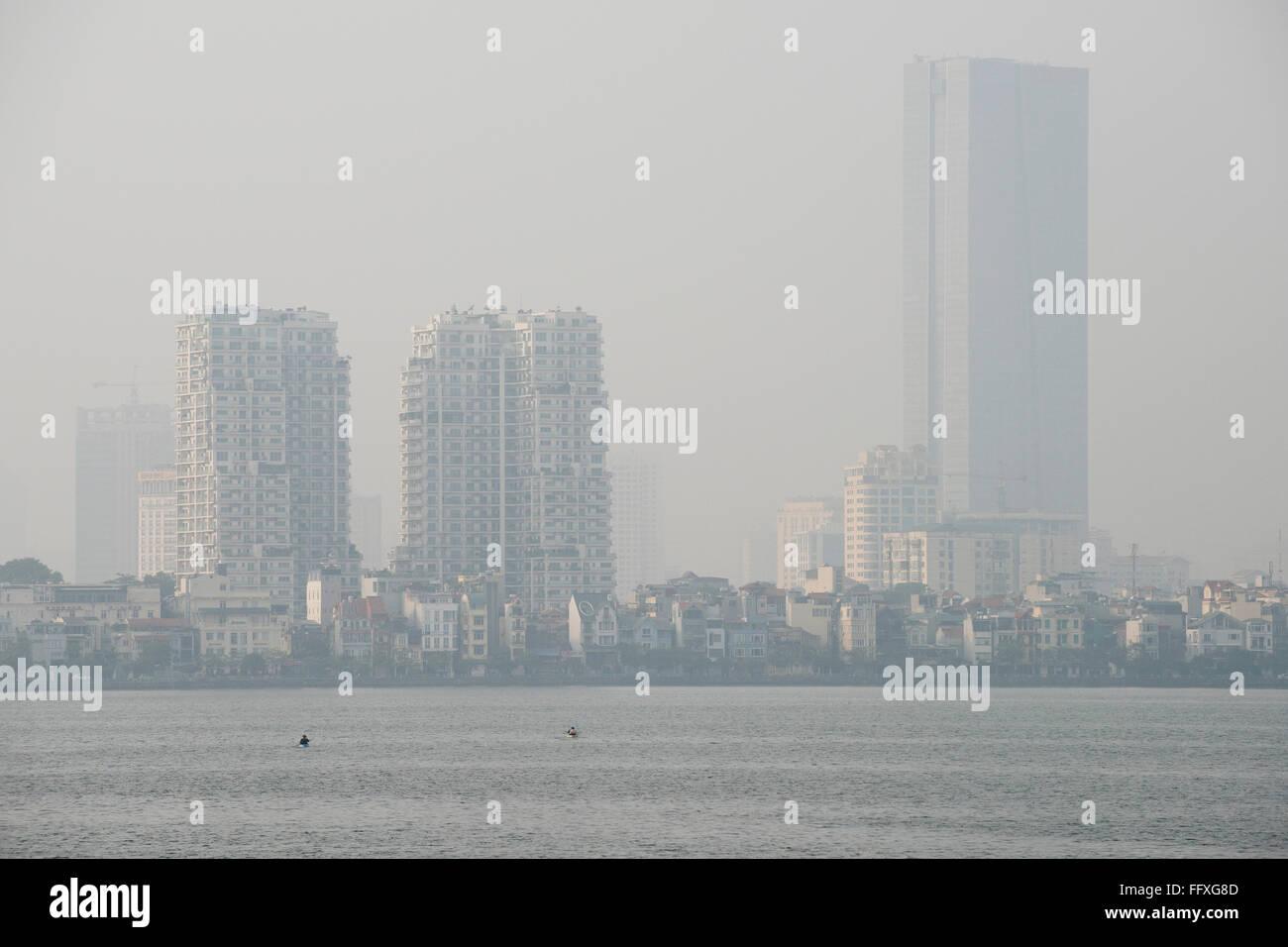 Mist, fog or smog pollution in a hazy skyline of Hanoi viewed over Westlake, Vietnam, January - Stock Image