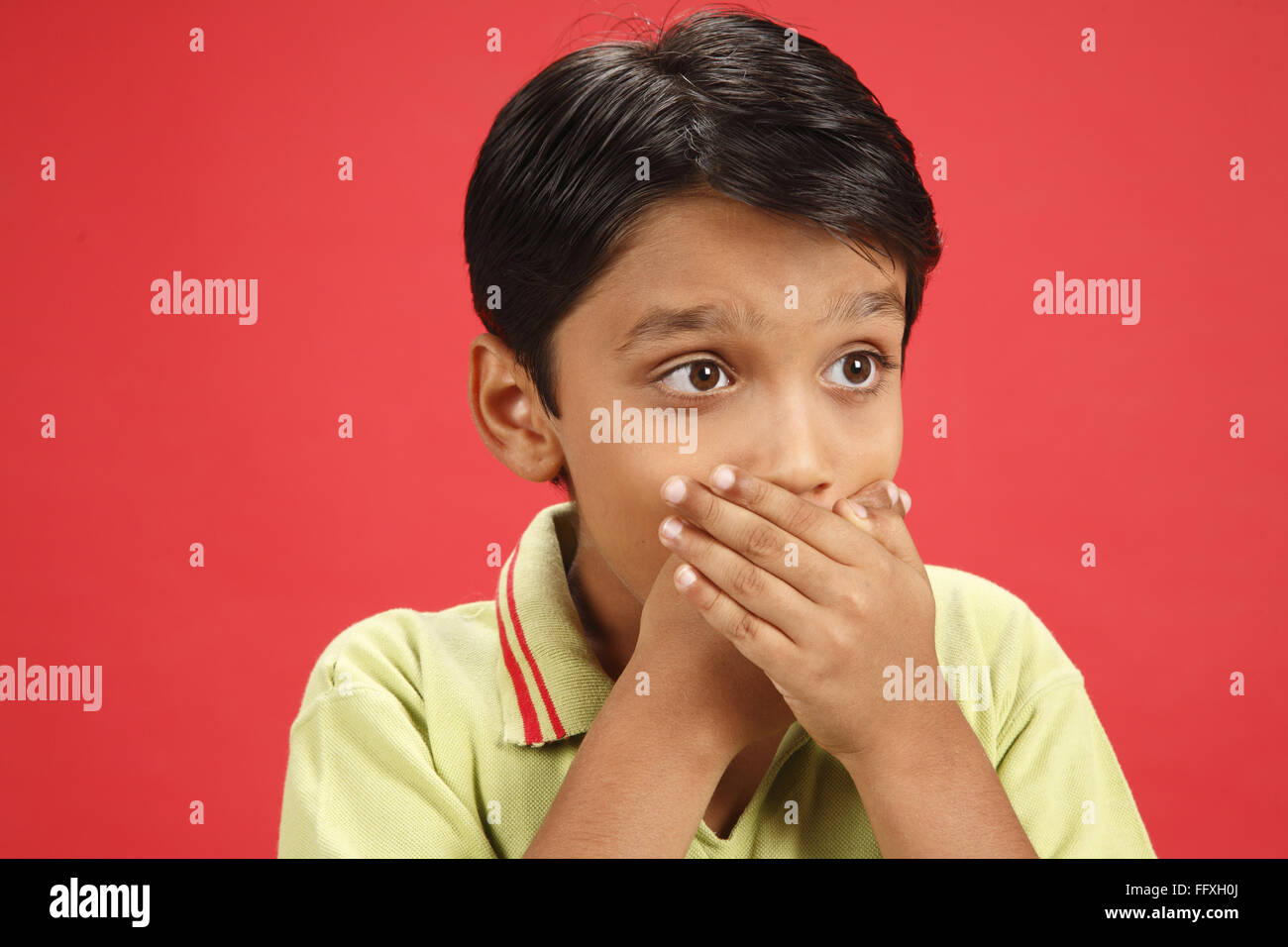 Ten year old boy kept both hand palms crossed on his mouth MR#703V - Stock Image