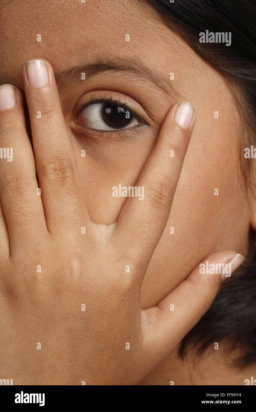 Eight year old girl kept her left hand on her face and seeing MR#703U - Stock Image