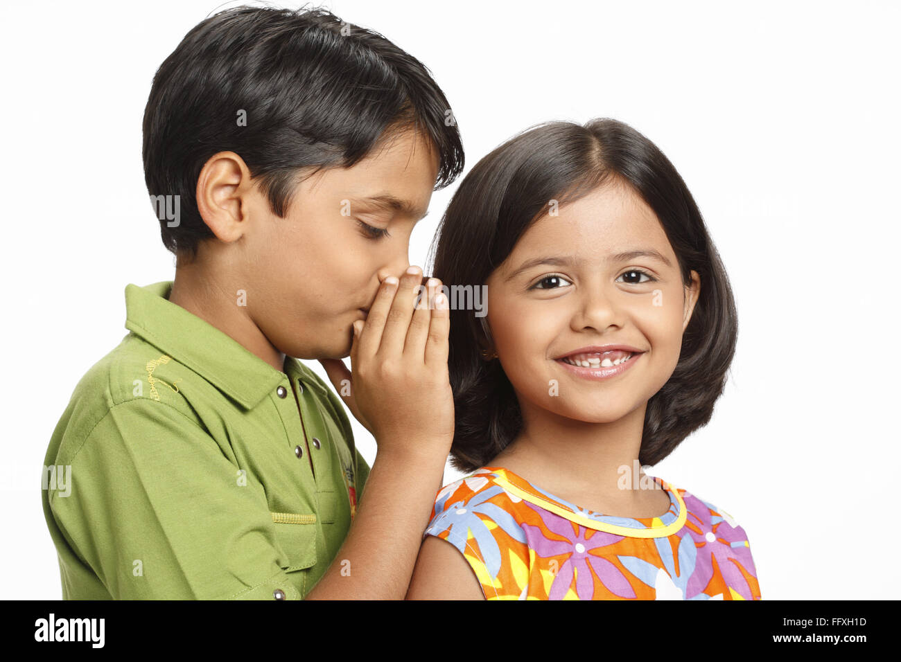 Ten year old boy whispering something in eight year old girl's ear MR# 703U,703V - Stock Image