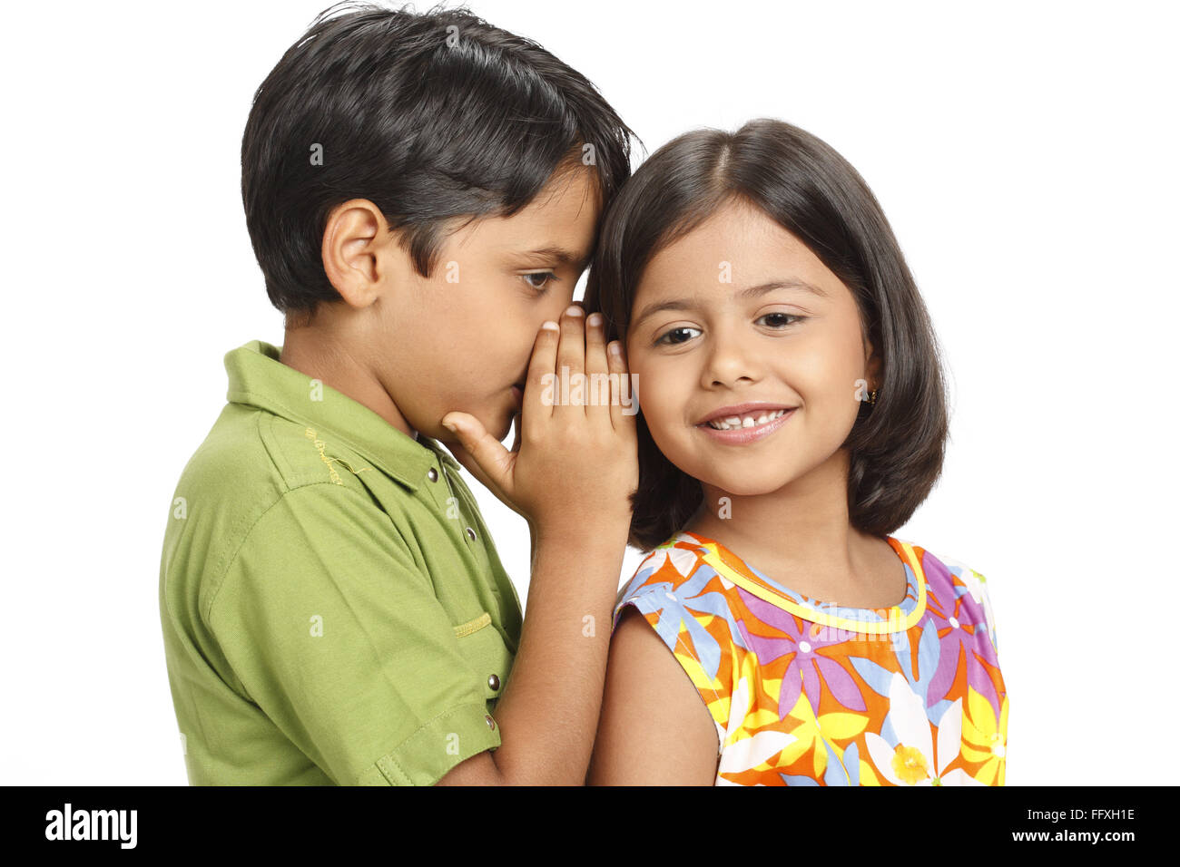 Ten year old boy whispering something in eight year old girl's ear MR# 703U,703V Stock Photo