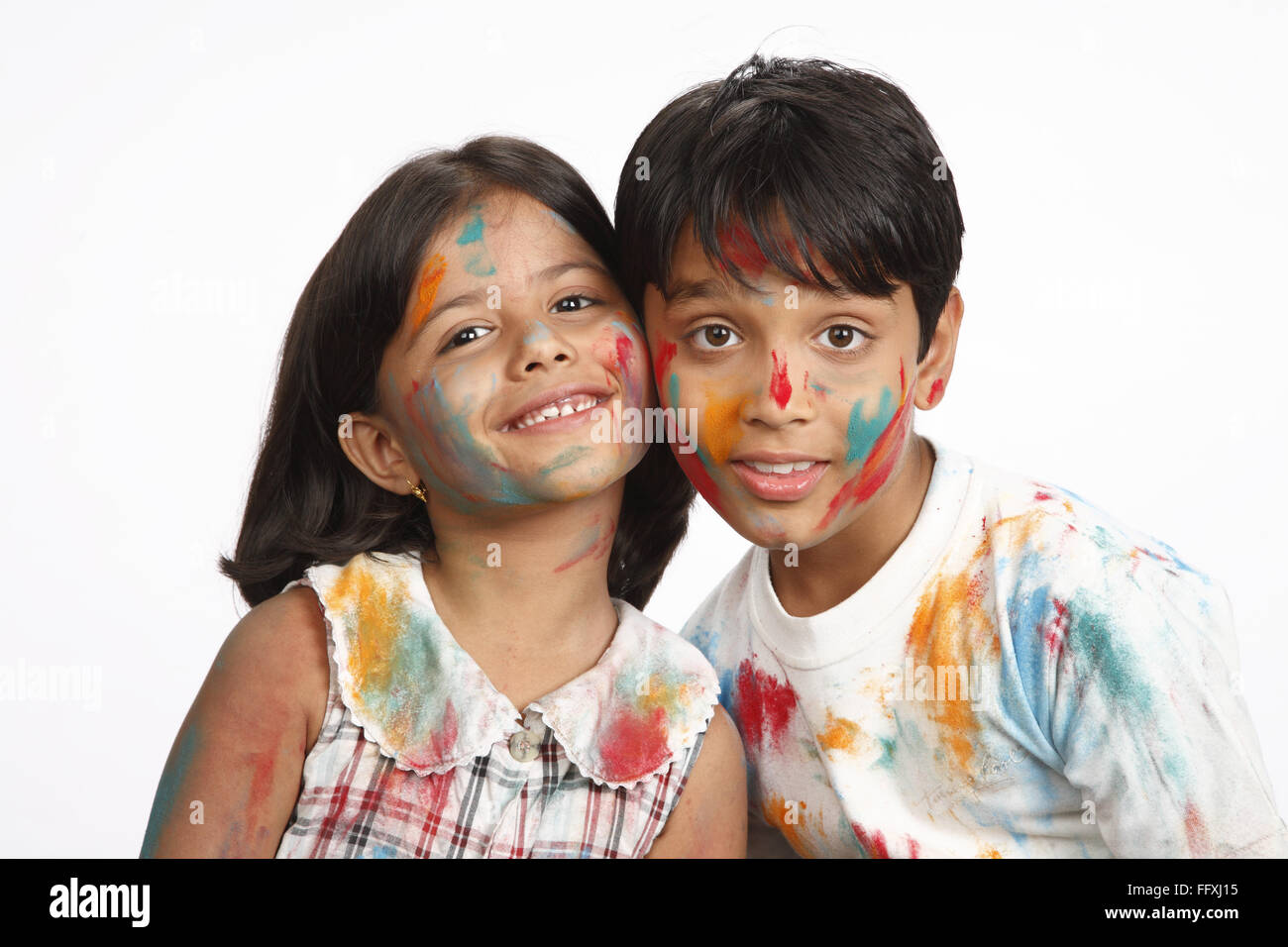 Ten and eight year old boy and girl posing with heads touched to each other on Holi festival MR# 703U,703V - Stock Image