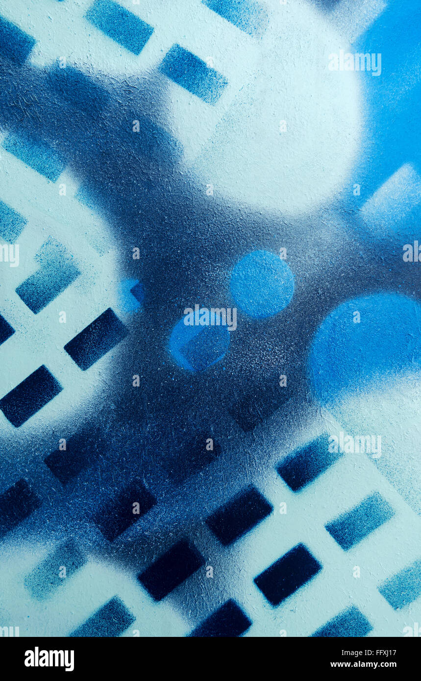 Abstract geometrical pattern sprayed with blue paints on a textured surface. Taken in vertical format. - Stock Image