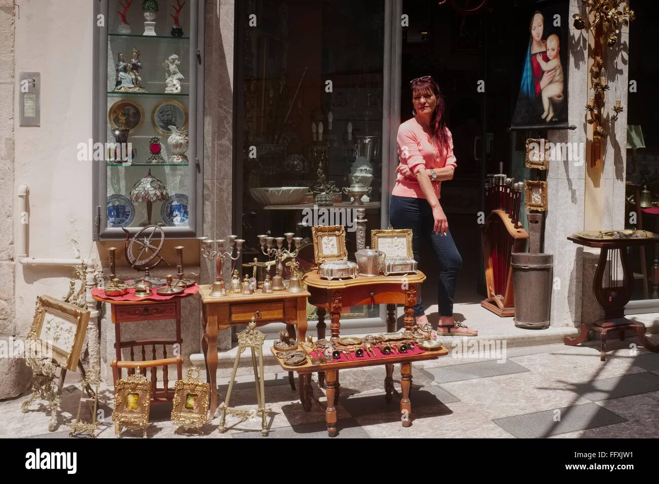 A lady shop keeper smokes a cigarette whilst waiting for customers to he antique shop just off the high street in - Stock Image