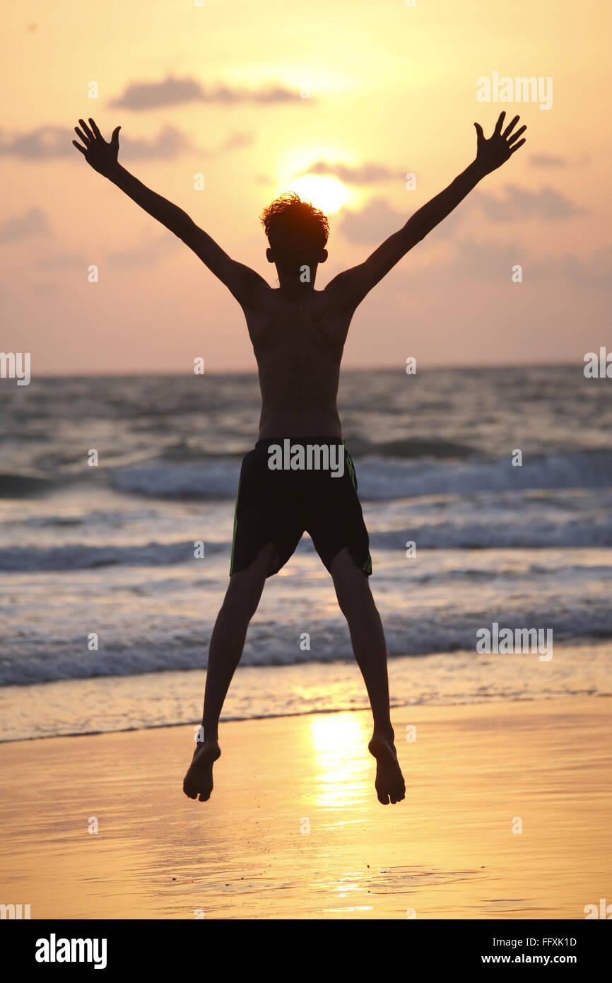Young boy taking high jump with hands wide open on seashore , Velagar , Shiroda , Sindhudurga , Maharashtra , India - Stock Image