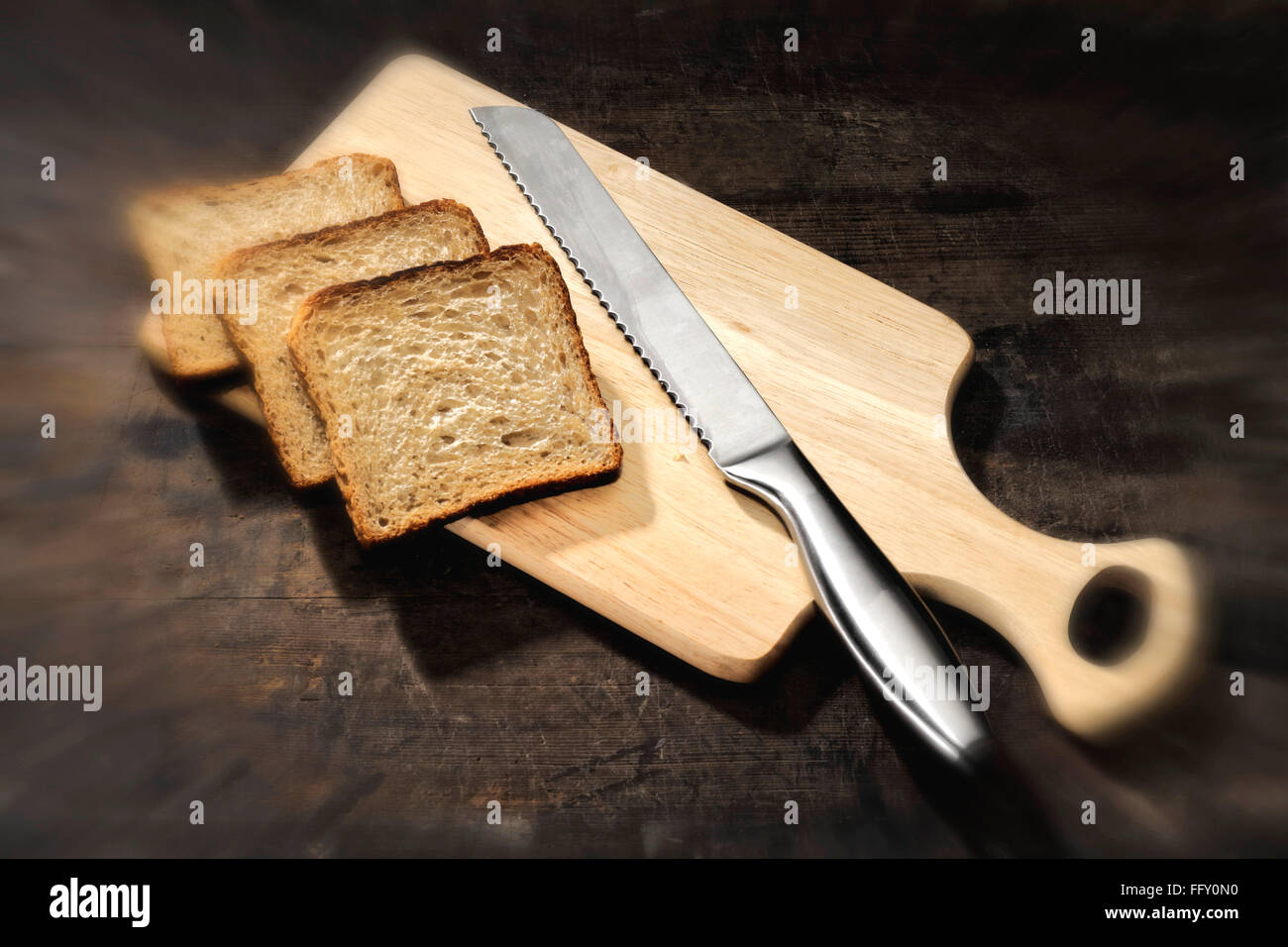 Kitchen things , bread with bread knife on wooden cutting board - Stock Image