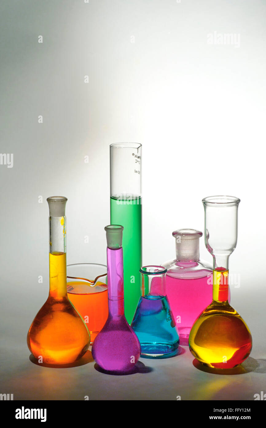 Concept , various colourful chemicals in beakers on white background - Stock Image