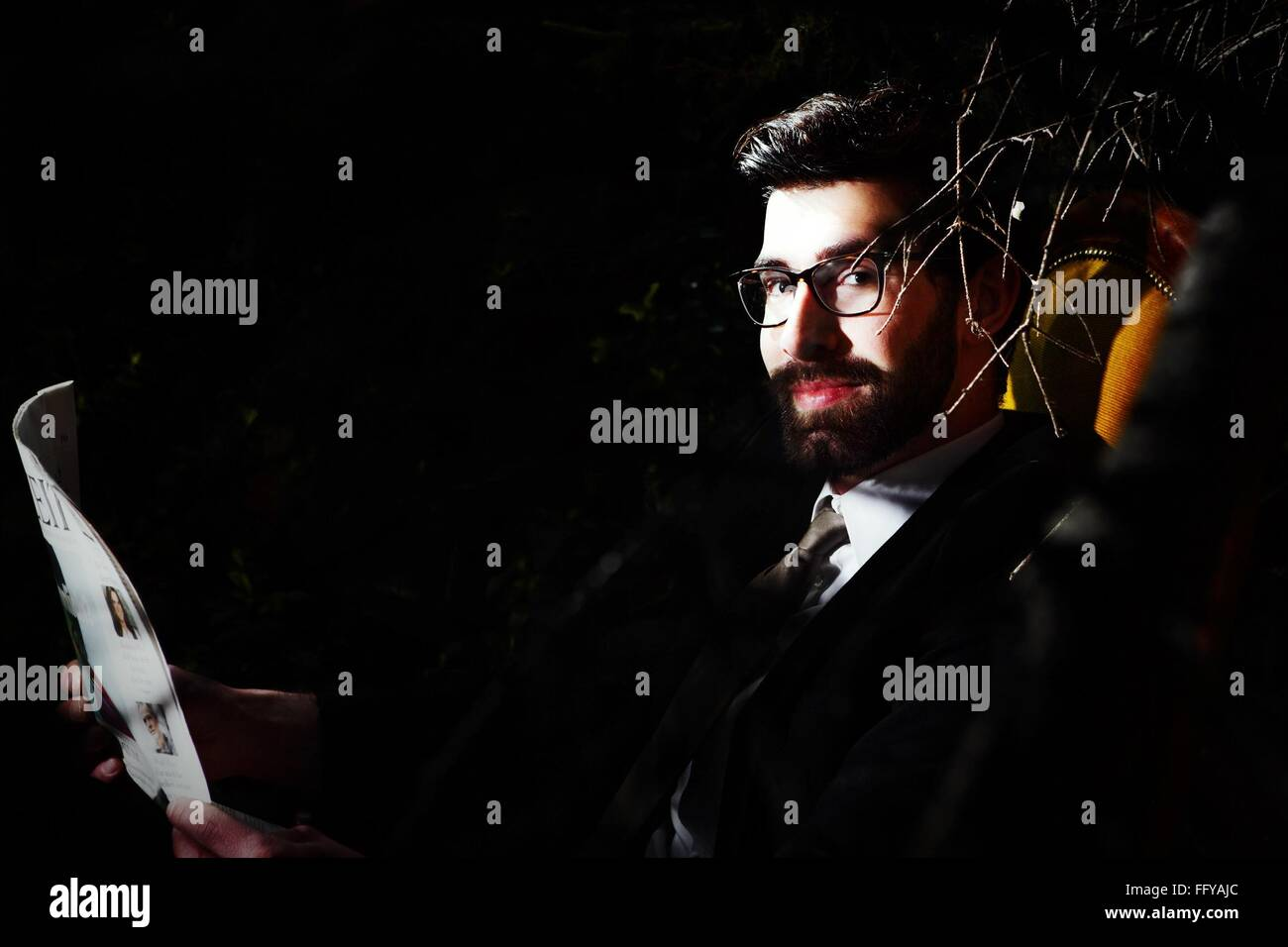 Portrait Of Well-Dressed Young Man Reading Newspaper In Park At Night - Stock Image