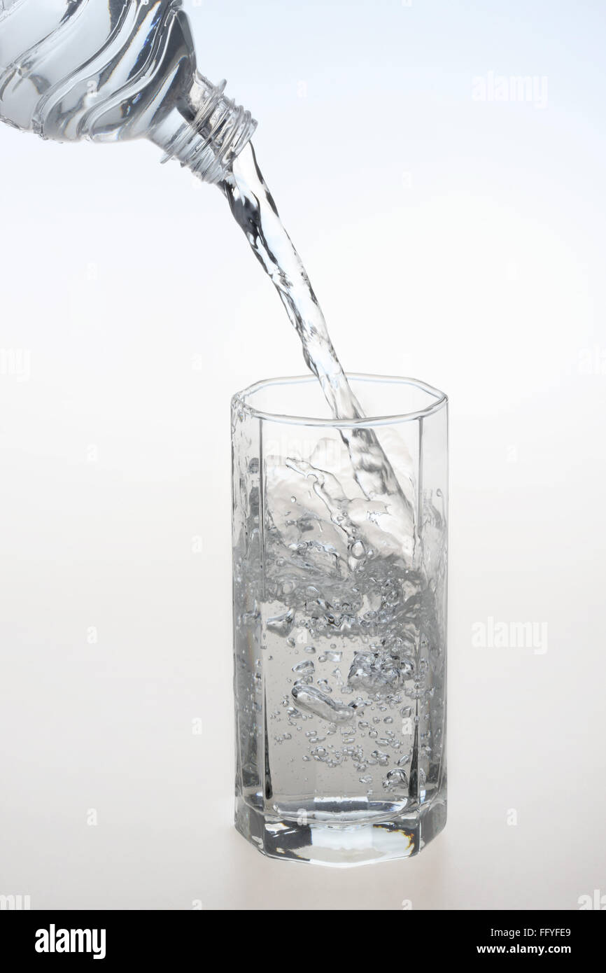 Pouring water in transparent crystal glass ; India - Stock Image