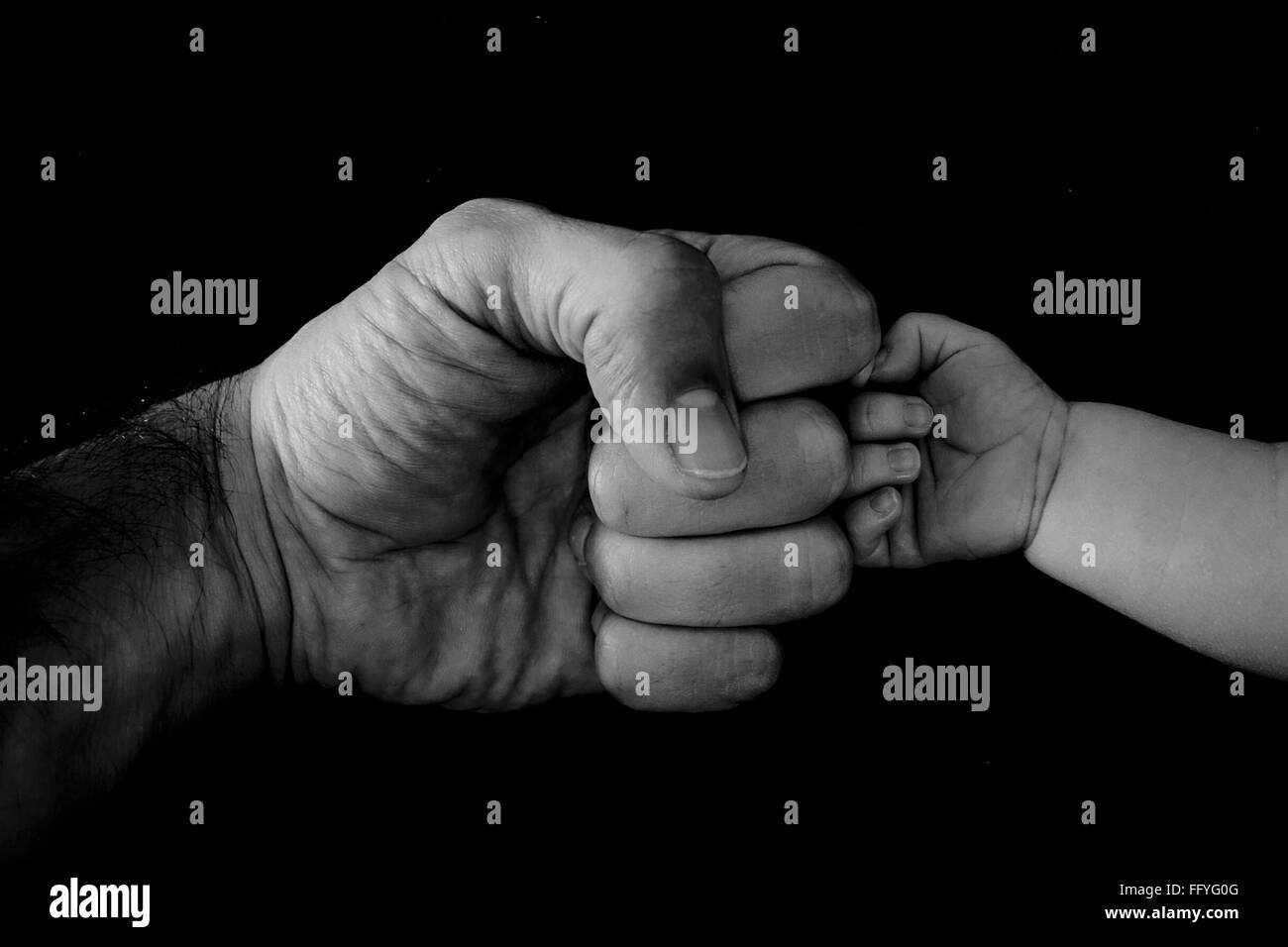 Cropped Image Of Father And Child Bumping Fist Against Black Background - Stock Image