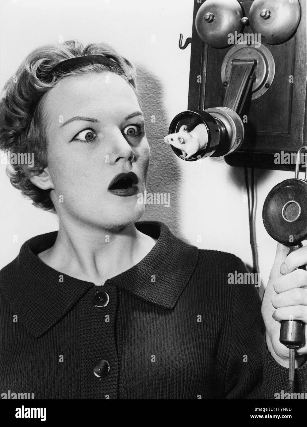 oddities, woman observing mouse in mouthpiece of an old telephone, 1950s, Additional-Rights-Clearences-NA - Stock Image