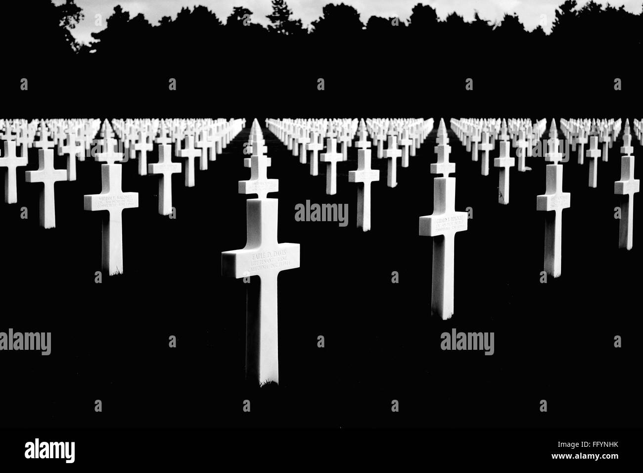 Cross In Cemetery Against Silhouette Trees - Stock Image