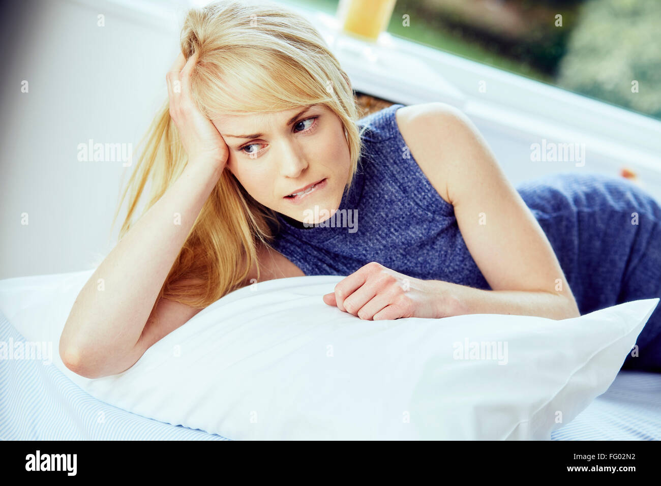 Stressed girl lying in bed - Stock Image