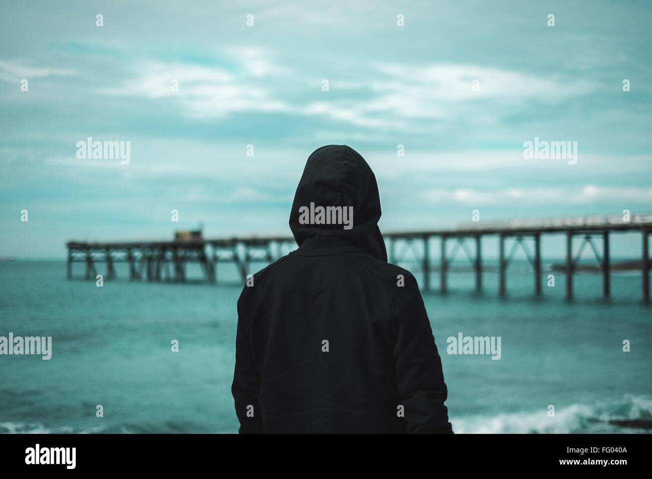 Rear View Of Man On Beach Against Sky At Dusk - Stock Image