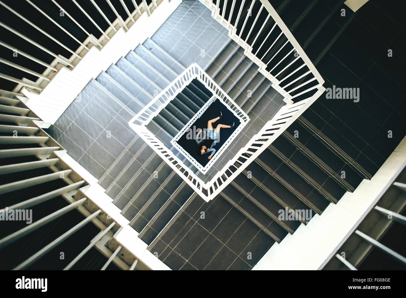 High Angle View Of Stairs With Woman Lying On Floor - Stock Image
