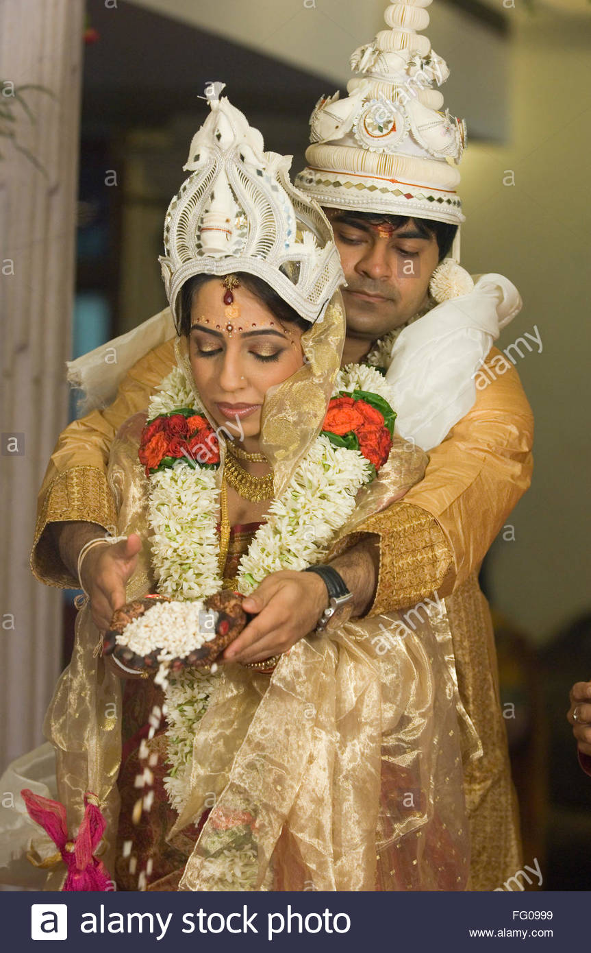 Bengali Bride And Bridegroom Performing Ritual Offering Puffed Rice