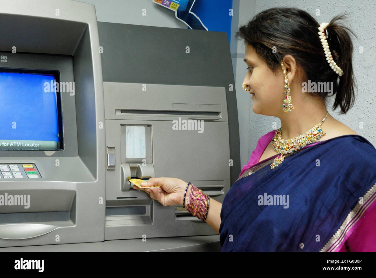 Lady using ATM card for withdraw cash from savings account at Maim , Bombay Mumbai , Maharashtra , India MR#721S - Stock Image