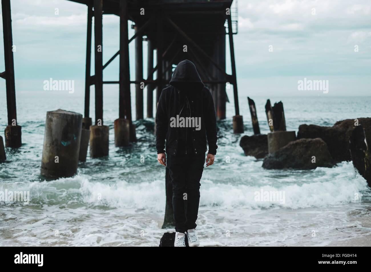 Mysterious Man Standing On Rock In Sea - Stock Image