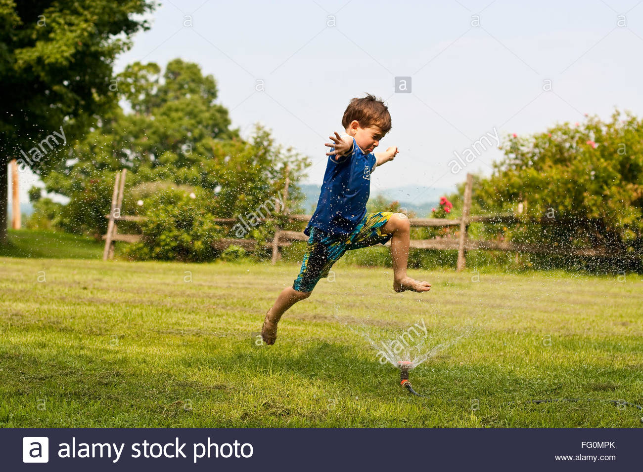 Side View Of Cheerful Boy Jumping Over Sprinkler At Lawn - Stock Image