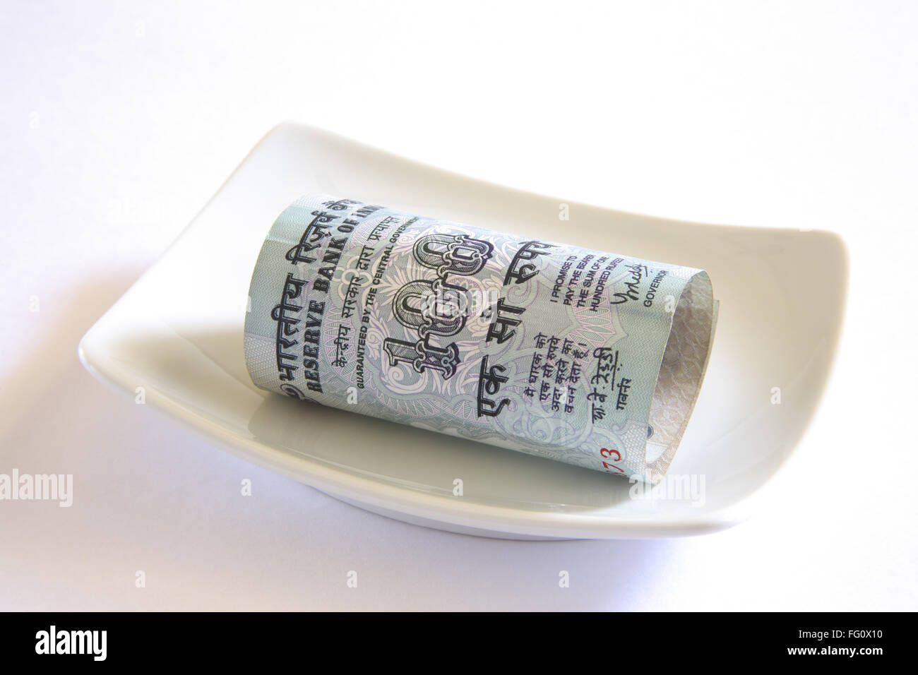 Concept , Indian currency one hundred rupees in plate - Stock Image