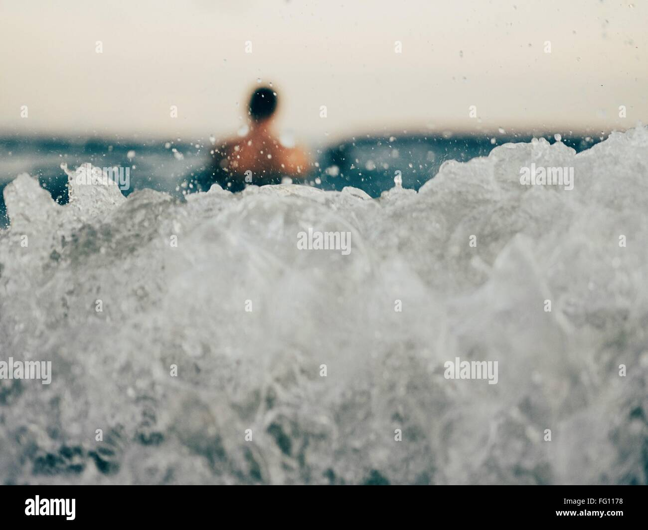Close-Up Of Wave With Blurred Man In Distance - Stock Image