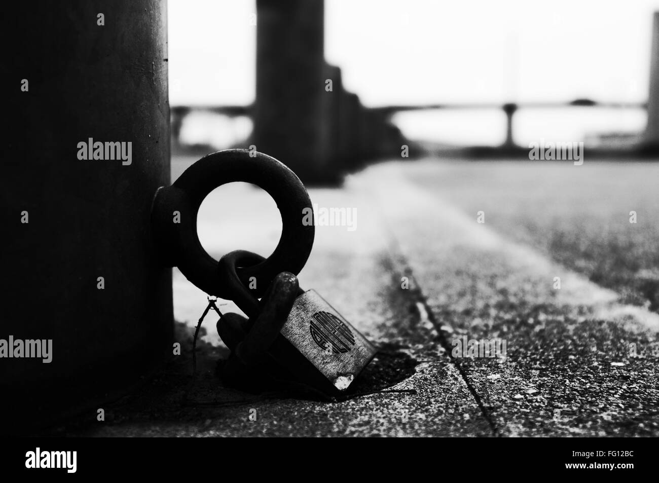 Close-Up Of Padlock Attached To Pole On Wooden Plank - Stock Image