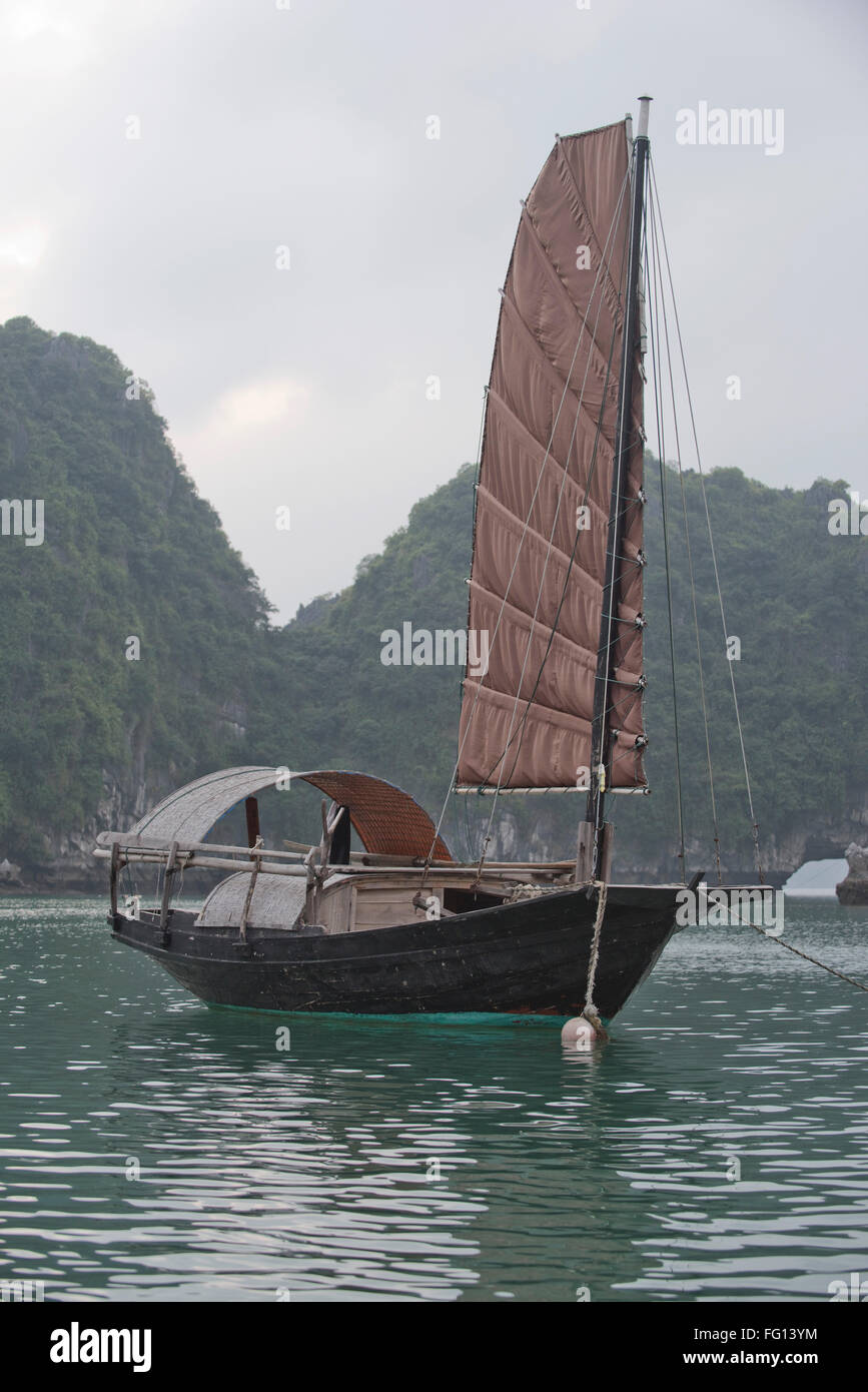 A single sailed junk moored in a fishing village in Halong Bay, North Vietnam - Stock Image
