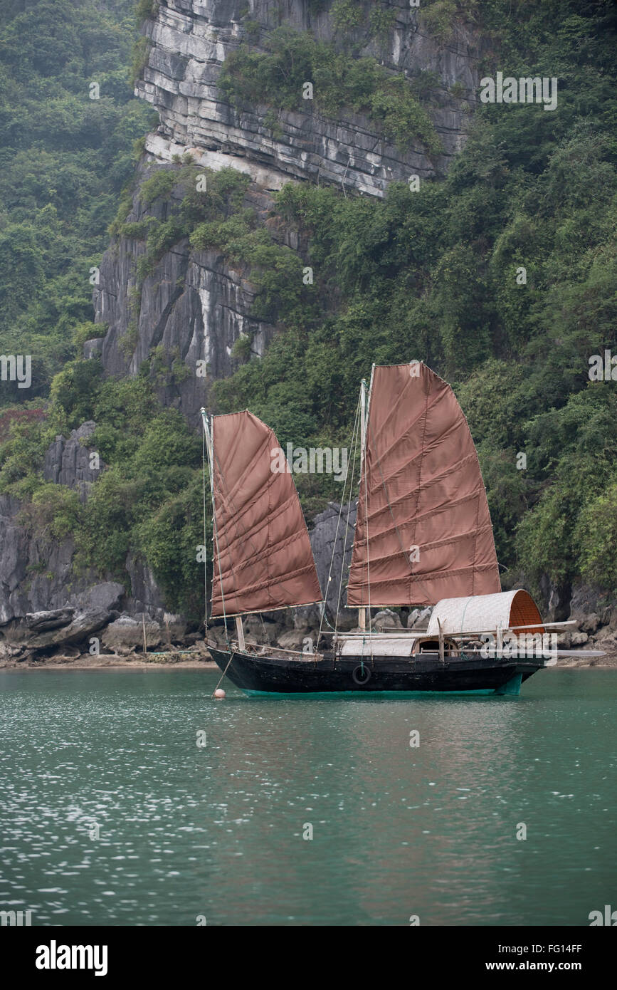 A twin sailed junk moored in a fishing village in Halong Bay, North Vietnam - Stock Image