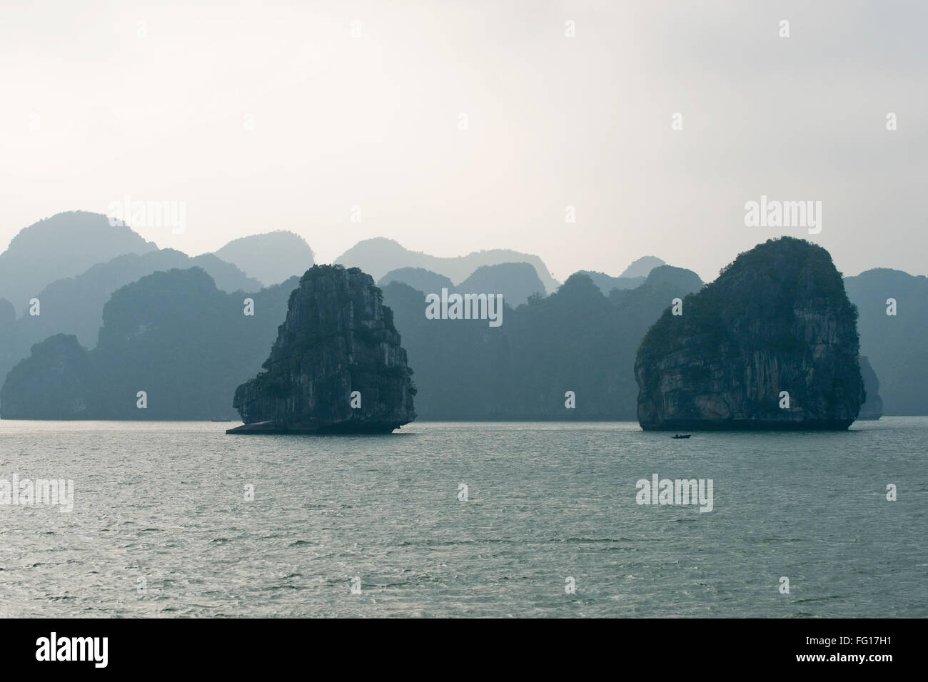 Misty image of receding  limestone karsts or islands rising out of the sea in Halong Bay, Northern Vietnam, - Stock Image
