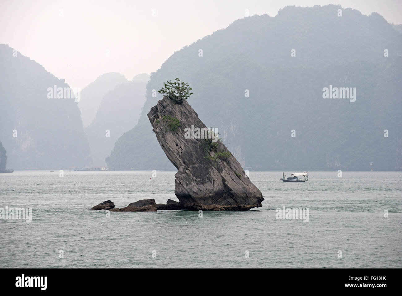 A small limestone karst, the remains of a much larger one after the island had eroded in Halong Bay. Stock Photo