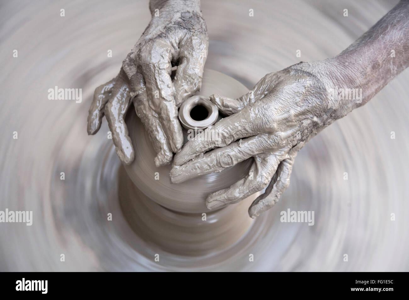 Pottery , artist muddy hands making clay pot giving shape on spinning wheel , semi urban village Dilwara , Udaipur - Stock Image
