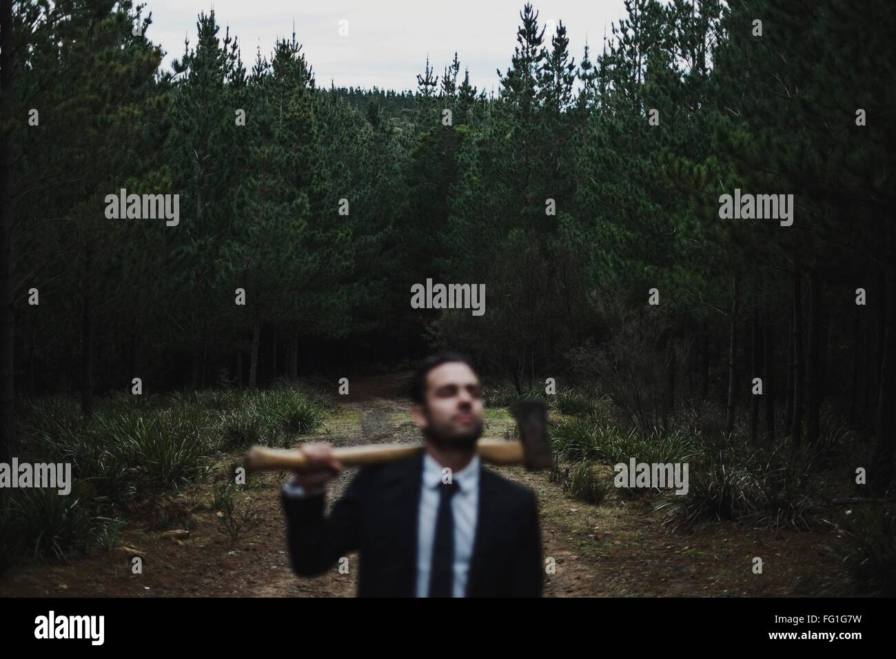 Man In Suit Holding Axe In Forest - Stock Image