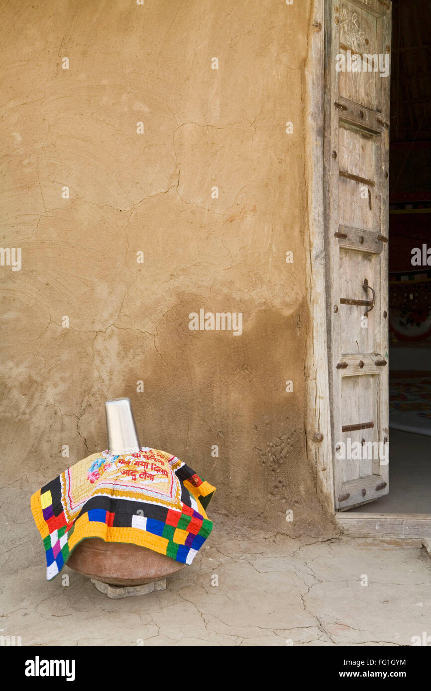 Earthen water pot with decorative cloth and steel glass kept outside house - Stock Image